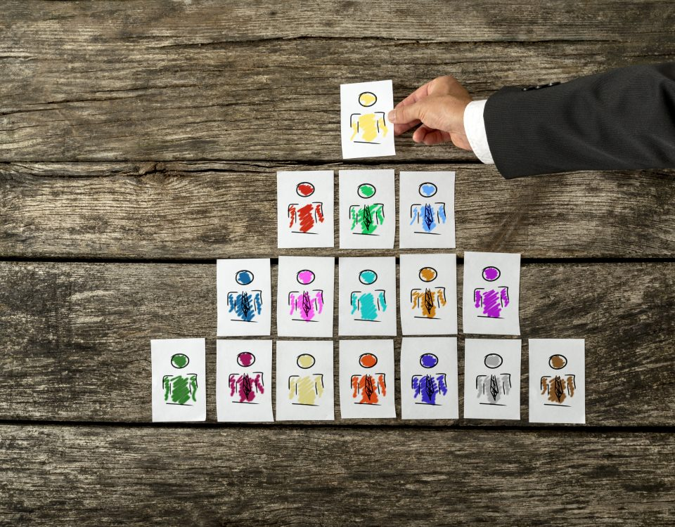 business psychologist arranging a series of hand-drawn cards depicting people into a pyramid