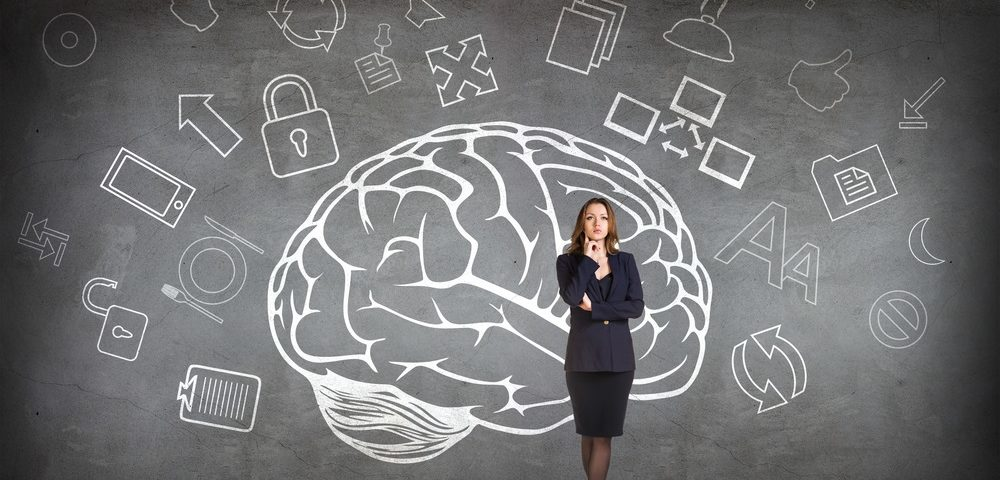 business woman standing in front of a blackboard with big brain drawn on it in chalk demonstrating business psychology