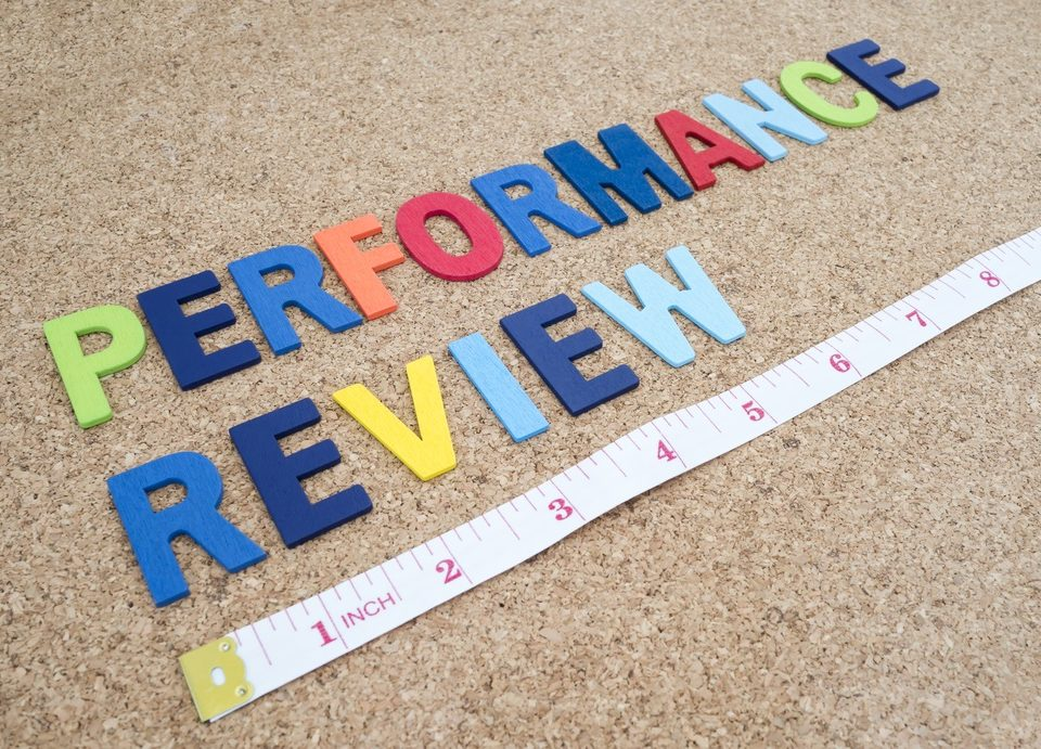 Performance review written in coloured letters on a carpet with a measuring tape underneath which signifies business psychologist aspect of employee management