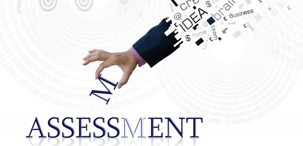 A hand reaching down towards the word assessment and placing the M into the word , above the wrist the arm is covered in a word bubble with phrases such as Idea & creative which all form a part of leadership assessment